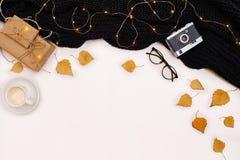 Accesorios del otoño para la mujer con las hojas y el café del amarillo con la leche, visión superior Imagen de archivo libre de regalías