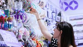 Accesorios del pelo del ` s de la mujer en alameda de compras la muchacha, mujer elige las horquillas, gomas, banda del pelo, en  metrajes