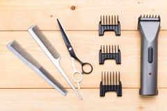accesorios del peluquero para el corte del pelo en un fondo de madera Imágenes de archivo libres de regalías