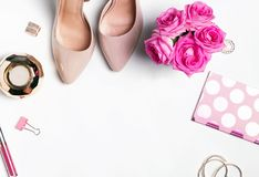Accesorios del ` s de la mujer y rosas rosadas en el fondo blanco Fotos de archivo