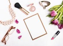 Accesorios del ` s de la mujer y tulipanes rosados en el fondo blanco Imagen de archivo