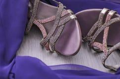 Accesorios del ` s de las mujeres Zapatos femeninos hermosos y bufanda púrpura en un fondo de madera Mirada de la manera Imagen de archivo