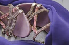Accesorios del ` s de las mujeres Zapatos femeninos hermosos y bufanda púrpura en un fondo de madera Mirada de la manera Imagenes de archivo