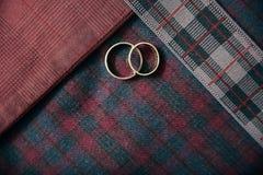 Accesorios del ` s de los hombres - anillos de bodas en fondo de la materia textil Imagen de archivo libre de regalías