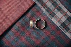 Accesorios del ` s de los hombres - anillos de bodas en fondo de la materia textil Fotos de archivo