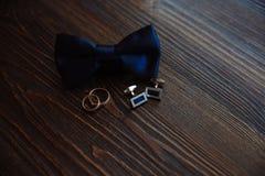 Accesorios del ` s de los hombres Corbata de lazo, mancuernas, anillos de oro Detalles del novio Imágenes de archivo libres de regalías