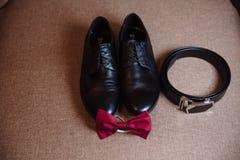 Accesorios del ` s de los hombres, corbata de lazo roja, zapatos, correa en la tabla Imagen de archivo libre de regalías