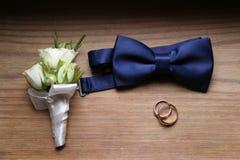 Accesorios del ` s de los hombres - corbata de lazo, anillos de bodas en fondo Imagen de archivo