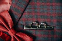 Accesorios del ` s de los hombres - corbata de lazo, anillos de bodas en fondo de la materia textil Imágenes de archivo libres de regalías