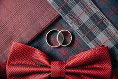 Accesorios del ` s de los hombres - corbata de lazo, anillos de bodas en fondo de la materia textil Imagenes de archivo