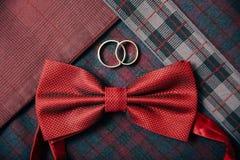 Accesorios del ` s de los hombres - corbata de lazo, anillos de bodas en fondo de la materia textil Fotos de archivo libres de regalías
