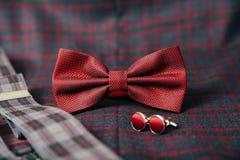 Accesorios del ` s de los hombres - corbata de lazo, anillos de bodas, mancuernas en fondo de la materia textil Fotos de archivo