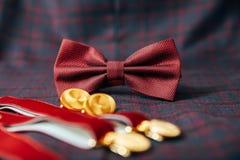 Accesorios del ` s de los hombres - corbata de lazo, anillos de bodas, mancuernas en fondo de la materia textil Foto de archivo