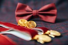 Accesorios del ` s de los hombres - corbata de lazo, anillos de bodas, mancuernas en fondo de la materia textil Imagen de archivo