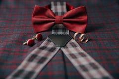 Accesorios del ` s de los hombres - corbata de lazo, anillos de bodas, mancuernas en fondo de la materia textil Fotografía de archivo
