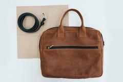 Accesorios del ` s de los hombres La correa de cuero y un bolso que mienten en una tabla Foto de archivo libre de regalías