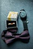 Accesorios del ` s de los hombres para el novio en la boda: relojes, corbata de lazo y anillos Imagen de archivo