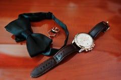 Accesorios del ` s de los hombres para el novio en la boda: relojes, corbata de lazo y rin Imágenes de archivo libres de regalías