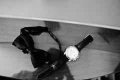 Accesorios del ` s de los hombres para el novio en la boda: relojes y corbata de lazo Imágenes de archivo libres de regalías