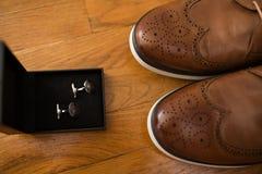 Accesorios del ` s de los hombres Zapatos de cuero de Brown y mancuernas de plata en una caja en un fondo de madera detalles Fotografía de archivo libre de regalías