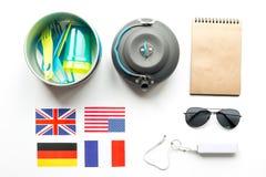 Accesorios del ` s del viajero en concepto de las vacaciones en la opinión superior del fondo blanco de la tabla Fotos de archivo libres de regalías