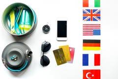 Accesorios del ` s del viajero en concepto de las vacaciones en la opinión superior del fondo blanco de la tabla Foto de archivo libre de regalías