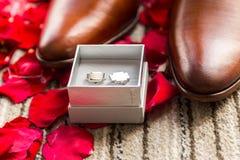 Accesorios del ` s del hombre de la boda en los pétalos color de rosa rojos Fotos de archivo