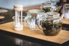 Accesorios del té en una madera Imagen de archivo