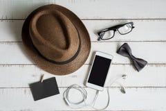 Accesorios del teléfono móvil y de los hombres en el fondo de madera blanco Foto de archivo libre de regalías