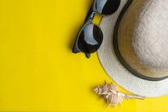 Accesorios del verano, cáscara del mar, sombrero y vidrios de sol en fondo amarillo Vacaciones de verano y concepto del mar imagen de archivo libre de regalías