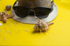 Accesorios del verano, cáscaras del mar, sombrero y vidrios de sol en fondo amarillo Vacaciones de verano y concepto del mar fotografía de archivo libre de regalías