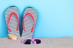Accesorios del verano con una concha marina en la arena Imagen de archivo