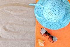 Accesorios del verano Sombrero y gafas de sol y una toalla en el mar foto de archivo
