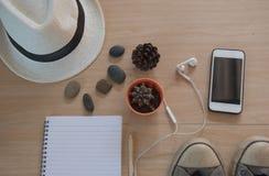 Accesorios del viaje del concepto de la visión superior Sombrero, libro, teléfono, zapatos, auricular en fondo de madera Imagen de archivo