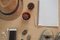 Accesorios del viaje del concepto de la visión superior Sombrero, libro, teléfono, zapatos, auricular en fondo de madera Foto de archivo libre de regalías
