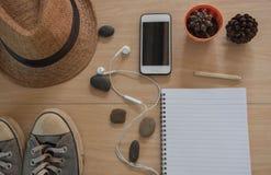 Accesorios del viaje del concepto de la visión superior Sombrero, libro, teléfono, zapatos, auricular en fondo de madera Foto de archivo