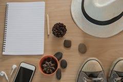 Accesorios del viaje del concepto de la visión superior Sombrero, libro, teléfono, zapatos, auricular en fondo de madera Fotos de archivo