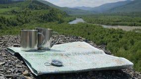 Accesorios del viaje a la aventura en montañas: taza, conpass y mapa en el fondo verde de la naturaleza Fotos de archivo