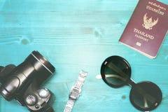 Accesorios del viajero en la tabla de madera azul y el vacatio esencial Imagen de archivo