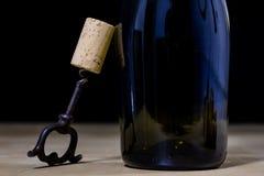 Accesorios del vino en una tabla de madera Corcho, sacacorchos y una botella Imagen de archivo