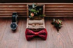 Accesorios elegantes del ` s del novio en un fondo de madera Corbata de lazo, boutonniere, y anillos de oro Fotografía de archivo libre de regalías