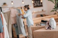 Accesorios elegantes en las cajas y el hombre que trabajan con ropa detrás en boutique Foto de archivo