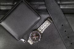 Accesorios elegantes para hombre del cuero negro, de la cartera, de la correa y de un reloj de acero en el fondo de una cartera n Imágenes de archivo libres de regalías