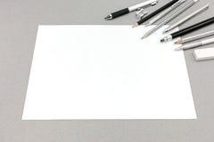 Accesorios en blanco de la hoja de papel y del dibujo en fondo gris Fotografía de archivo