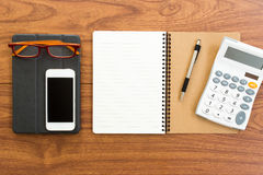 Accesorios en blanco del cuaderno y de la oficina en la tabla de madera Imagen de archivo libre de regalías