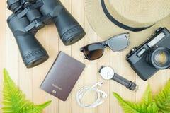 Accesorios esenciales de los artículos del viajero, hoja tropical en la parte posterior de madera Foto de archivo