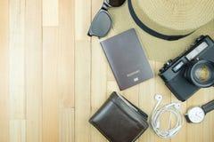 Accesorios esenciales de los artículos del viajero, hoja tropical en la parte posterior de madera Imágenes de archivo libres de regalías