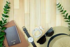 Accesorios esenciales de los artículos del viajero, hoja tropical en la parte posterior de madera Fotos de archivo