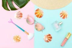 Accesorios femeninos Belleza y viaje en fondo del color de pasteles imagen de archivo
