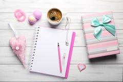 Accesorios femeninos con el cuaderno, la taza de café y la caja de regalo en w Imágenes de archivo libres de regalías